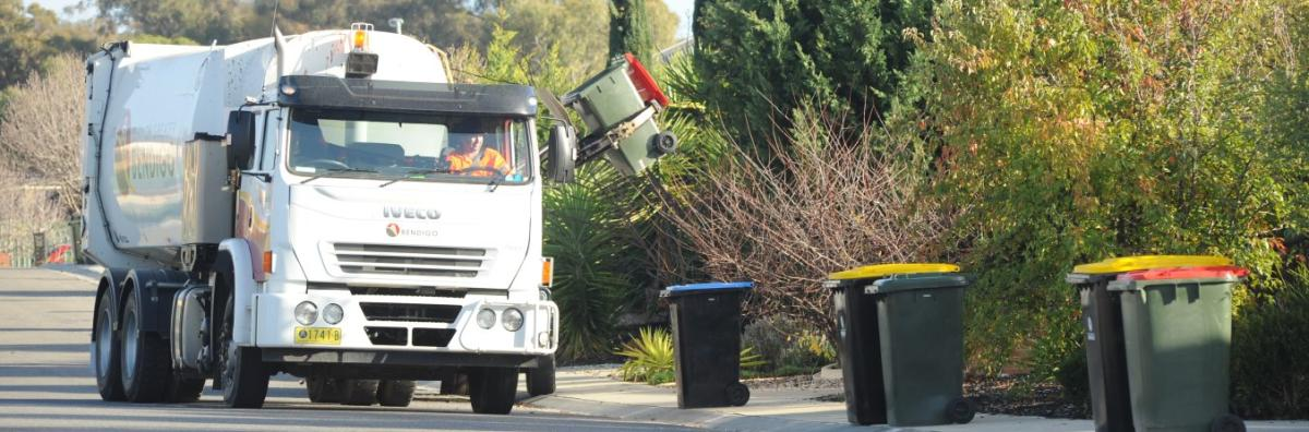 Rubbish truck on street with bins