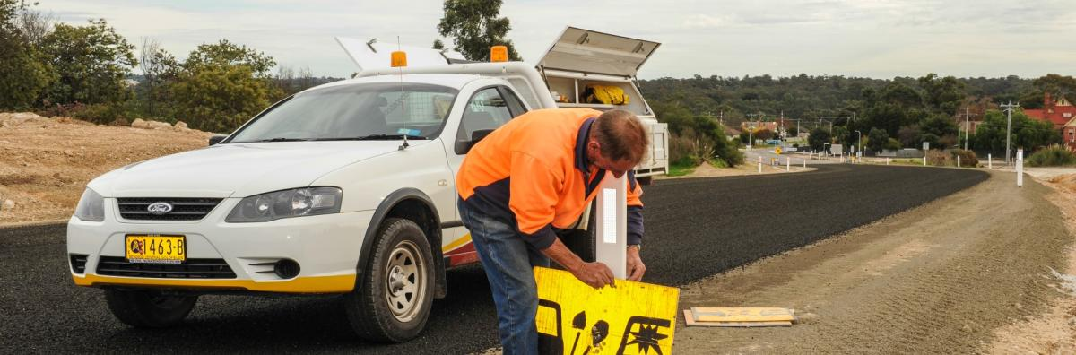 Staff member putting roadworks sign up