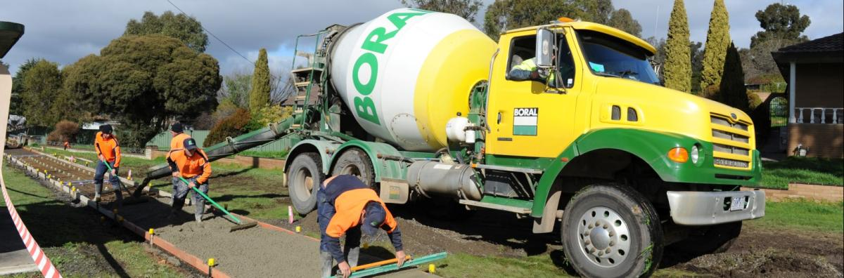 Staff smoothing concrete on new footpath