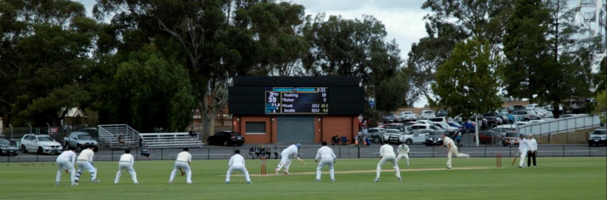 People in white playing cricket