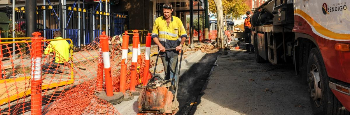 Staff using equipment for roadworks