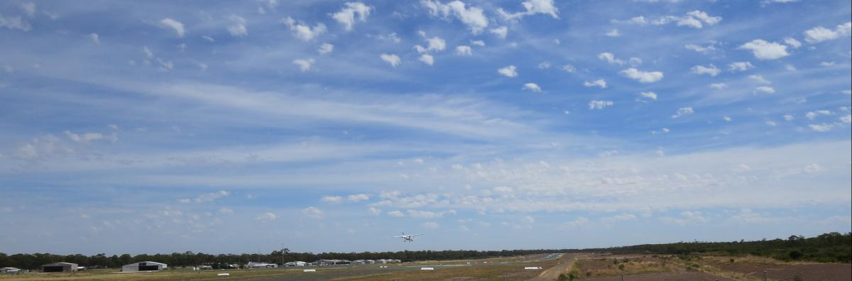 wide view of small aircraft landing on Bendigo airport runway