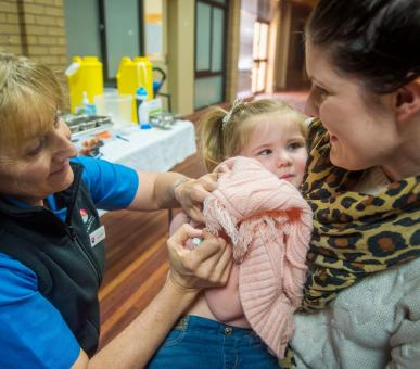 Immunisation nurse gives a vaccine to a toddler