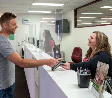 A male customer stands at a counter with a female customer service attendant behind a perspex screen. they maintain social distancing while using the EFTPOS machine. They're both smiling.