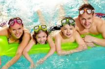 Family with Goggles Floating in Pool