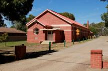 The Axedale Public Hall and Preschool is a brick building with shaded parking and a playspace next door.